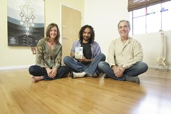 PHOTO BY STEVE E. MILLER - TWISTS AND TURNS :  Ahmed Fahmy, who's flanked by Karen and Bryan Duggan, teaches children yoga techniques and environmental care on an award-winning, locally produced DVD.