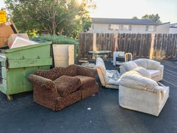 PHOTO BY KASEY BUBNASH - IS THIS THE DUMP? Couches, chairs, tables, and a mini-fridge sit outside an apartment complex near Cal Poly just before San Luis Garbage's fall Cleanup Week.