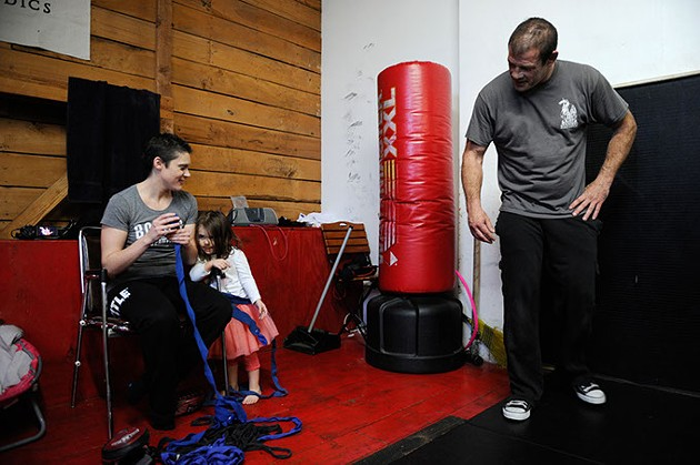 Scarlett Hoffman, 2, helps her mother, Rebecca, roll boxing tape as Travis Hoffman looks on at Western Avenue Boxing in Oklahoma City, Dec. 3, 2014. - GARETT FISBECK