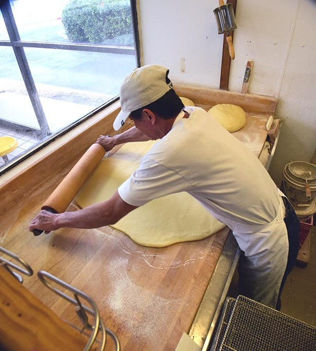 Sok San has been the baker at North May Donuts & Kolaches for over 5 years, shown rolling out kolache dough on the recent busy Christmas Eve morning.  mh