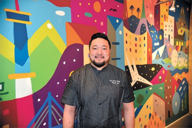 Chef Kevin Lee stands in front of a mural by artist Kris Kanaly representing Lee's influences at Gogi Go. | Photo Jacob Threadgill