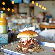 The Full Boar sandwich is piled high with pulled pork, brisket, a hot link and coleslaw.
