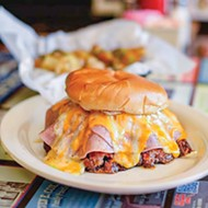 A Buster Burger is a sausage burger topped with ham, chili and cheese.