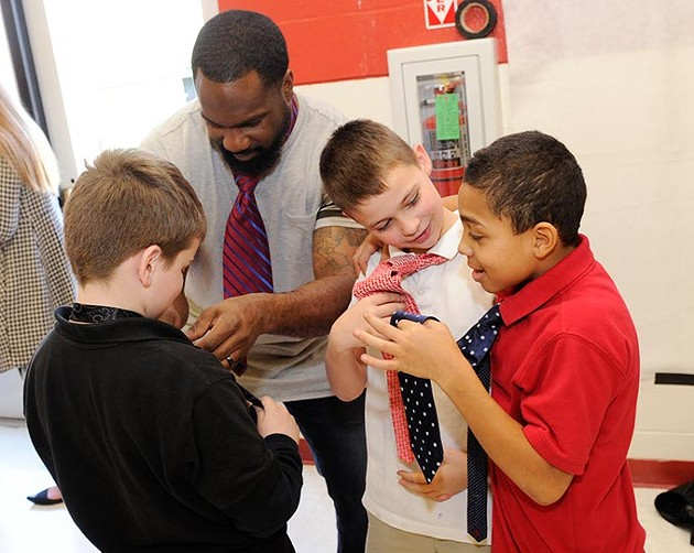 Waylon Kiesewetter and Joshua Shinault show off their ties while Joel Tudman shows Dayton Mitchell how to tie a tie during Tie Day at Edgemere Elementary in Oklahoma City, Thursday, Jan. 14, 2016. - GARETT FISBECK