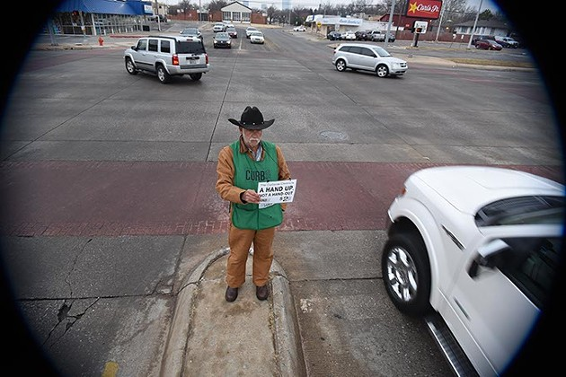 """Gary """"Cowboy"""" Fields, a Curbside Chronicle vendor, on the median at Broadway Avenue and N.W. 23rd Street, the last day before city ordinance prohibiting panhandling from medians like this, takes effect, 1-6-16. - MARK HANCOCK"""