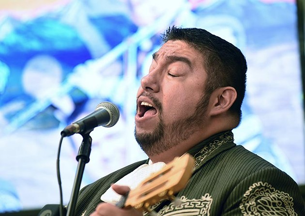 Robert Ruiz takes the lead vocal with the band Mariachi Orgullo de America, performing in the center court at Plaza Major at the Crossroads mall, Sunday afternoon.  mh