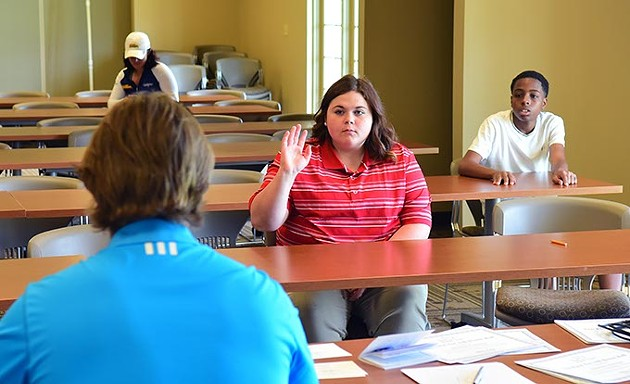 Kirstin Westlake raisers her hand to answer a question during a short classroom session with director Dustin Semsch and others in her age group before the young golfers hit the course on a recent Saturday.  mh