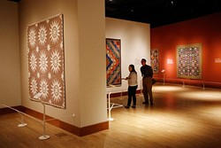 Seth Spillman and Tabbi Burwell look at quilts during the Quilts and Color Media tour, Wednesday, November 4, 2015. - GARETT FISBECK