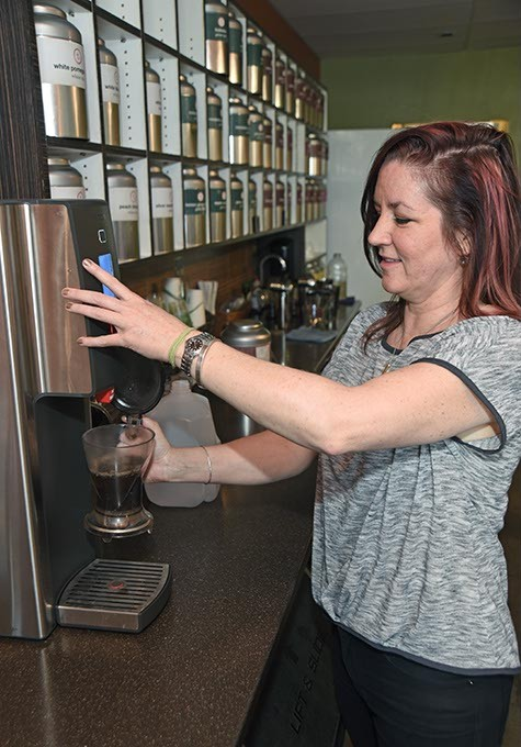 Kristy Jennings dispenses hot water into the black currant tea leaves during the iced tea making process.  mh