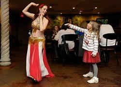 Theda Borja Lothrop, 6, tips Sevi Amar as she dances at Zorba's in Oklahoma City, Nov. 22, 2014. - GARETT FISBECK