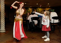 Theda Borja Lothrop, 6, tips Sevi Amar as she dances at Zorba's in Oklahoma City, Nov. 22, 2014. - GARETT FISBECK