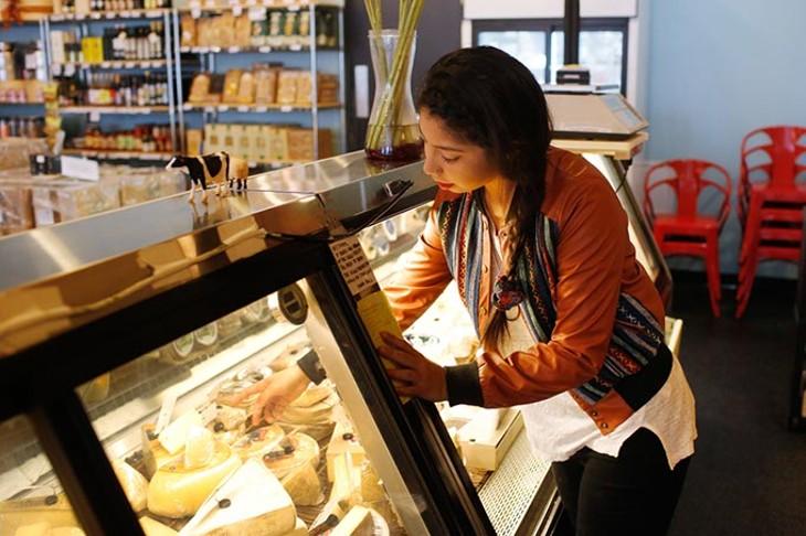Katelyn Polly checks a cheese display at Forward Foods. - GARETT FISBECK