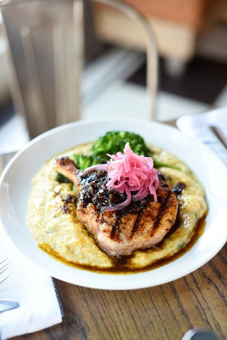 Pork chop w/ grits, broccoli, bacon jam and pickled onions at Packard's New American Kitchen, Thursday, March 31, 2016. - GARETT FISBECK