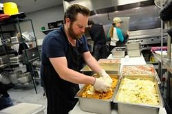 Russ Johnson helps  preps lunch at WestTown day shelter in Oklahoma City, Tuesday, March 24, 2014. - GARETT FISBECK