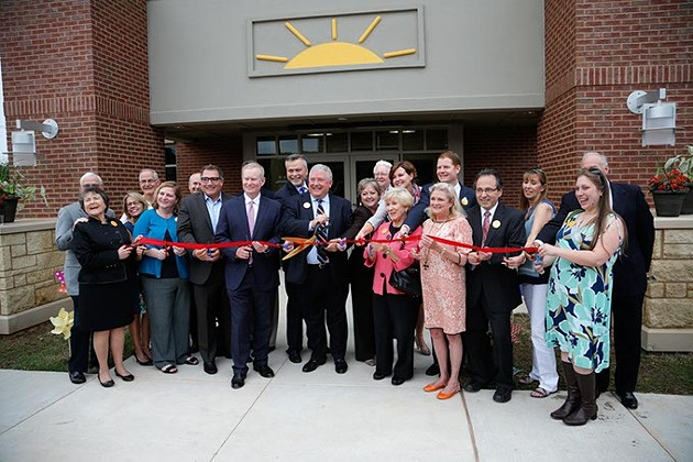 Dignitaries cut a ribbon during a grand opening ceremony at Sunbeam Family Services in Oklahoma City, Thursday, May 7, 2015. - GARETT FISBECK