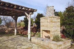 A rustic pergola next to an outdoor fireplace, part of the lanscaping on the grounds of Tony's Tree Plantation which will be exhibiting at this year's Oklahoma City Home and Garden Show.  mh