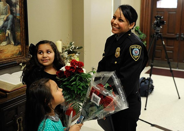 Alma Deloera recieves flowers from her daughter, Tatiana, 7, and her niece, Belle Reyna, 6, after the Oklahoma City Police Academy Recruit Class 132 graduation at First United Methodist Church, Thursday, Dec. 4, 2014. - GARETT FISBECK