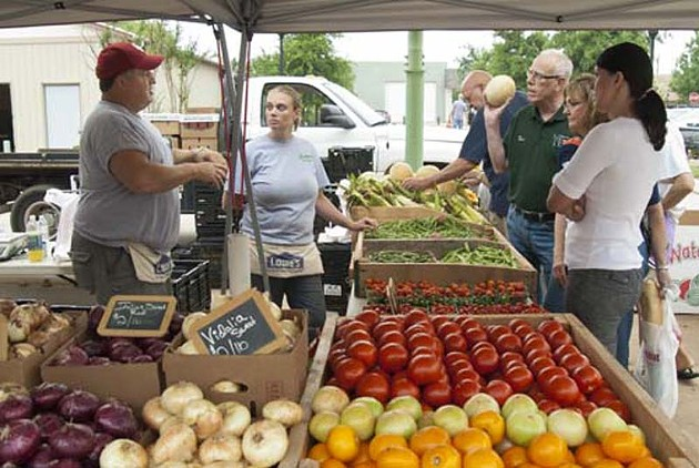Greg Loman of Loman's Landscape Design and Garden Center, left, discusses produce with customers, next to Loman's Melissa Abbey, Saturday Morning, 5-31-14, at the Edmond Market.  mh