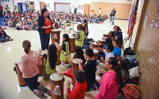 Rebecca Vaughn, music instructor at Prairie Queen Elementary School, leads her students on a short rhythmic arrangement, during an assembly presenting the approximately 40 new African drums donated to the school by the OKC Midtown Rotary, on Friday, 9-11-15. - MARK HANCOCK