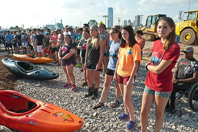 Young athletes watch the proceedings next of kayaks during the groundbreaking ceremonies for the newly named River Sport Rapids along the Oklahoma River in the Boathouse districe, Monday, 10-20-2014.  mh