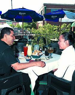 Left, Ruben Fuentes with Laura Gomez, pose at a table setting on the patio at the Bricktown Chelino's.  mh  both are employees with Ruben being the GM.