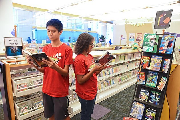 Alberto Liu and Jessica Jones, volunteers with the Summer Reading Program, help young readers get signed up, in the Ronald J. Norick Downtown Library.  mh