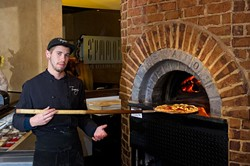 Dylan Lynch makes a pizza in Tommy's wood fire oven. (Shannon Cornman)