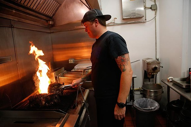 Kody Hookstra cooks pork at Frank's Wurst, located inside 51st Street Speakeasy. (Garett Fisbeck)