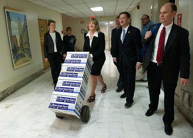 Tina Kelly wheels a stack of petitions to allow Independent voters to vote during the primaries to the State Election Board at the Oklahoma State Capitol in Oklahoma City, Monday, Feb. 22, 2016. - GARETT FISBECK