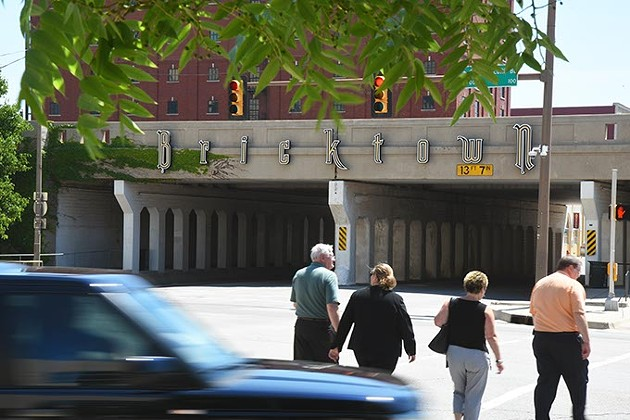 Pedestrians on their way to Bricktown cross E.K. Gaylord Boulevard at Sheridan near the train overpass, underwhich the new Maps Streetcars will pass.  mh