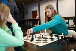 Veronika Zilajevs plays against her younger sister Victoria during a ladies' chess club meeting at District House in Oklahoma City, Saturday, Feb. 30, 2016. - GARETT FISBECK