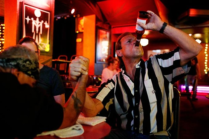 Mark Hughes takes a drink of his beer as he arm wrestles Al Rojas Jr. at the Hilo Club in Oklahoma City, Friday, Nov. 6, 2015. - GARETT FISBECK