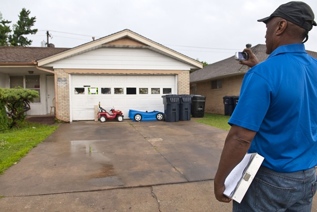 Ron Pollard, municipal code officer I, for the City of OKC, takes a photo after arriving at a vacant property at 1324 SW 43rd during an inspection, 6-19-14.  mh