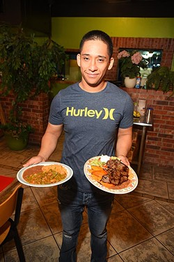 Son of owner, Oscar Zapata with Guisada de Puerco Verde con nopales, left, and Enchiladas Potosinas, at El Potosino restaurant, 2500 S. Robinson Avenue.  mh