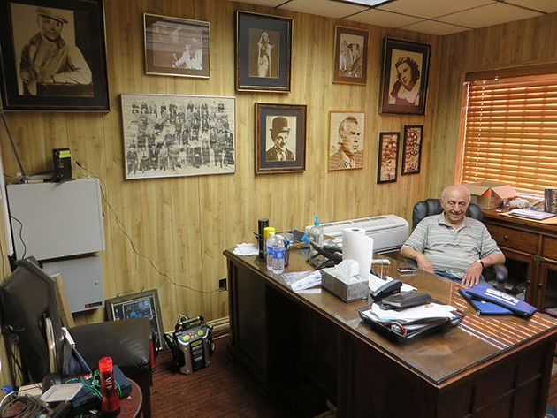 Lindy Shanbour sits in his busy office amid prized movie posters that he has collected during his long career in the movie business. - BRETT DICKERSON