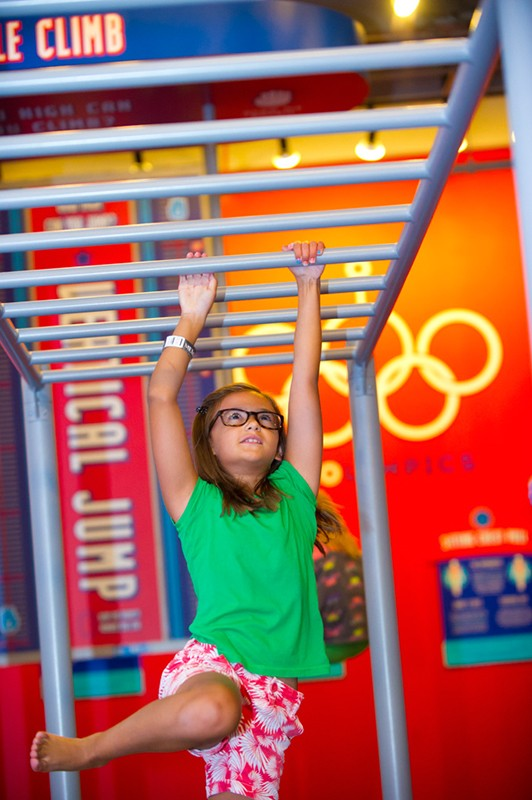 Skylar Lawrence works her way across the horizontal ladder at the fairly new Power Play exhibit at Science Museum of Oklahoma. - SHANNON CORNMAN