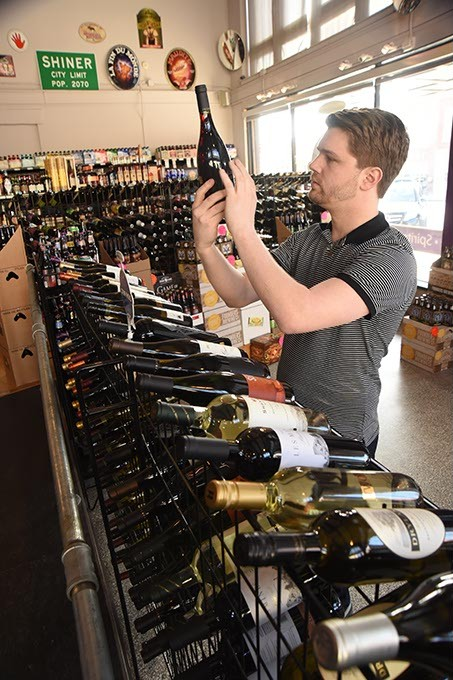 Employee Adam Rott reads a wine label at Broadway Wine Merchants in Auto Alley.  mh