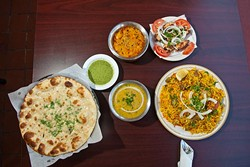 Assortment of Sheesh Mahal food includes, from left, garlic naan, daal, butter chicken, malai tikka chicken and a plate of rice biryani. (Mark Hancock)