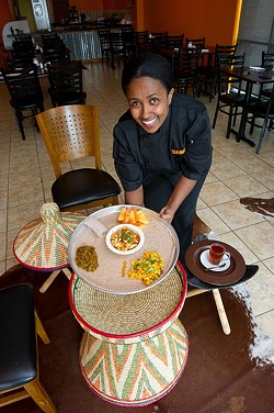 Haiget A Yosef brings Ethiopian and Kenyan cuisine Chicken Tibs with three sides, mango salad, gomen/sukamawiki, and yedenich wot to the mesob woven serving table. (Shannon Cornman)