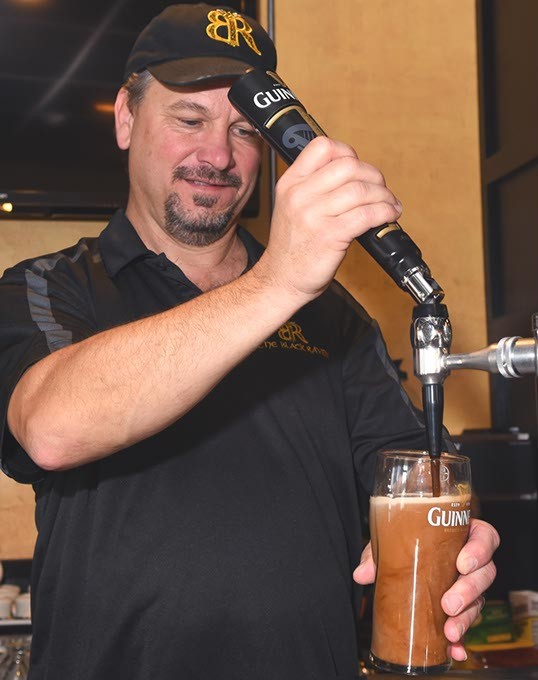 Black Raven Pub co-owner, Bryan Newport, draws a Guiness at the Choctaw Irish pub.  mh