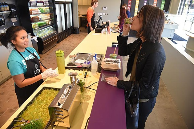 Customer Linsey Liles, at right, does a Wheat Grass Shot, sampling before purchasing, from Victoria Stevenson at the new Organic Squeeze Kitchen Table location in The Edge apartments in MidTown, Oklahoma City, 1-14-16. - MARK HANCOCK