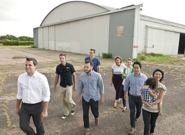 Blair Humphreys, left, leads a group of Design Team members and followers of the Wheeler District Downtown Airpark development effort in front of a hanger onto the surrounding airstrip recently.  mh