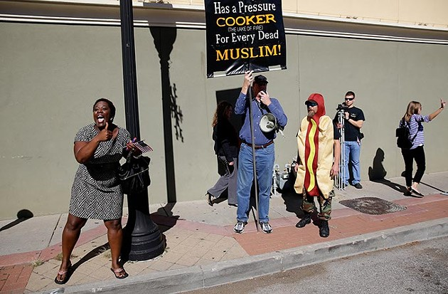 Kuma Roberts left shouts support to Muslims marching with the Oklahoma branch of the Council on American-Islamic Relations during the Tulsa Veterans Day Parade Nov. 11, 2015. At right Jim Gilles protests the inclusion of Muslims in the parade. (Photo Mike Simons / Tulsa World / File / Provided)