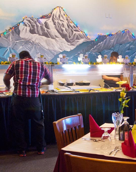 The Himalayas mountain range over the Buffet line, while workers tend to the offerings, for lunch at Himalayas Aroma of India.  mh