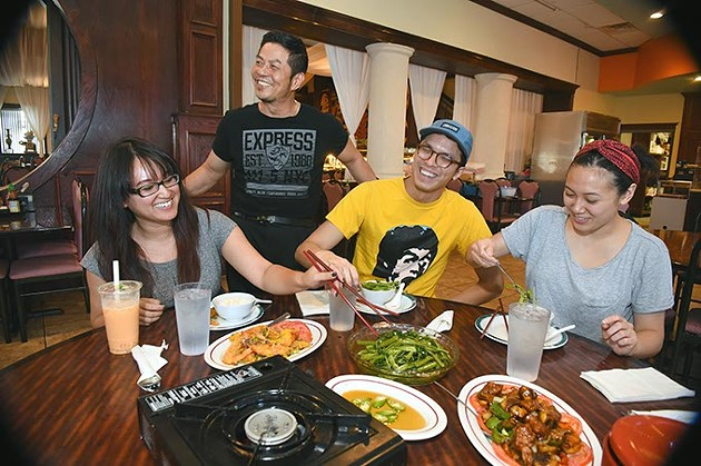"1st generation Asian Americans, seated from left, Michelle Bui, Chris ""Quit"" Nguyen, and Linda Phan, enjoy a nice variety of food brought out by Johnny Hy, owner of Hy Palace, during a recent get together.  mh"
