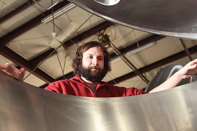 Jonathan Stapleton part owner of 405 Brewing Company in Norman, looks into one of the large stainless steel brewing vesels.  mh