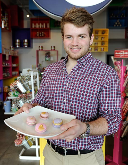 Carson Park holds a plate of macaroons (cinnamon, raspberry, hazelnut, blueberry) at Uptown Candy Co. in Oklahoma City, Wednesday, Jan. 28, 2015. - GARETT FISBECK