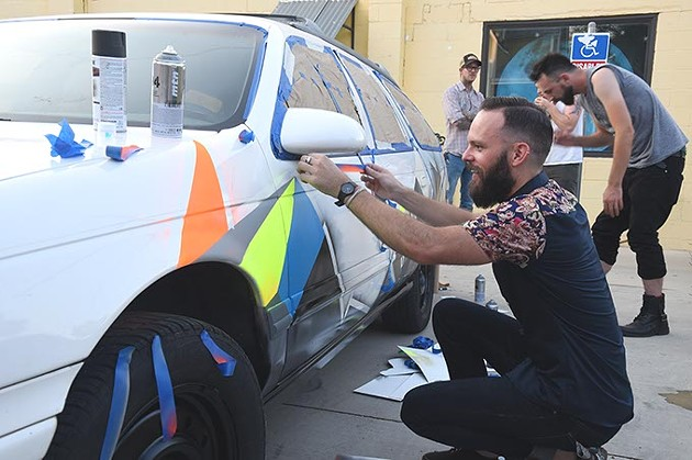Jerrod Smith, owner of The Society collective art studio, puts a paintjob on a old Ford stationwagon, with help from fellow collective artists as part of the 4 year celebration at and in the parking lot of the art space in the Plaza District, 8-14-15.  mh