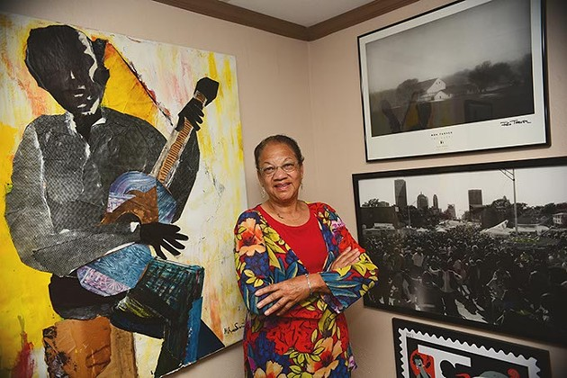 Anita Arnold, executive director of BLAC, with artwork in her office including a large work of Charlie Christian by artist Melvin R. Smith, a graduate of Fredrick A. Douglas High School like Charlie Christian.  mh