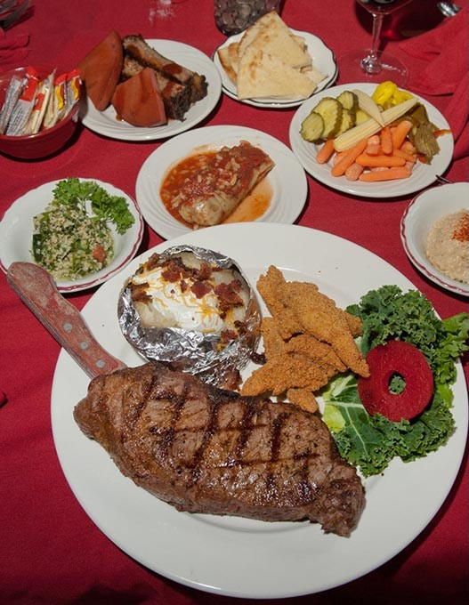 Gigantic KC Strip steak with fried catfish, baked potato, tabouleh and more sides, adorn a table at Jamil's Steakhouse.  mh